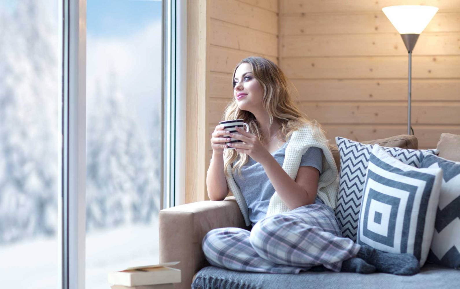 image of woman on sofa enjoying the benefits of radiant heat panels